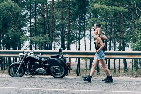 side view of young couple of bikers walking along road and embracing near black motorcycle and green forest
