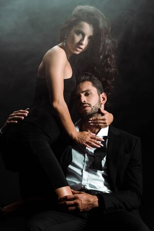 woman standing and embracing bearded man on black with smoke