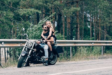 young couple of bikers hugging while sitting on black motorcycle on road near green forest