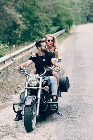 young couple of bikers on black motorcycle on road near green forest Stockfoto