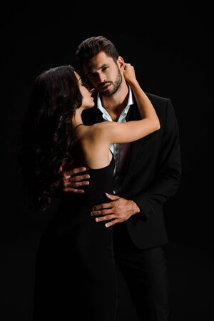 attractive girl hugging handsome bearded man looking at camera isolated on black Stockfoto