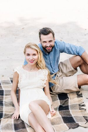 beautiful smiling young couple sitting on plaid blanket at sandy beach Stockfoto