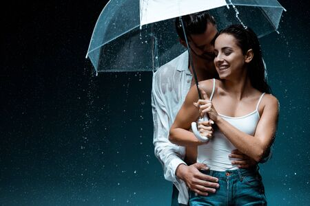cheerful girl holding umbrella and standing with handsome boyfriend under raindrops on black Stockfoto