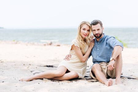 beautiful young barefoot couple sitting on blanket at beach near sea