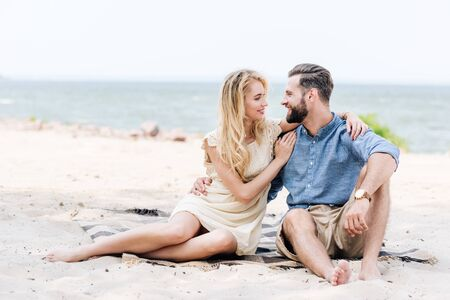 happy beautiful young barefoot couple sitting on blanket and looking at each other at beach near sea
