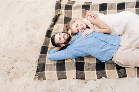 happy couple lying together on plaid blanket at sandy beach