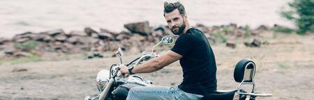 handsome bearded motorcyclist on black motorcycle at sandy beach near sea, panoramic shot Stockfoto