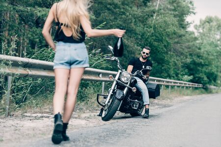back view of young woman walking on road with bottle of alcohol near boyfriend on black motorcycle on road