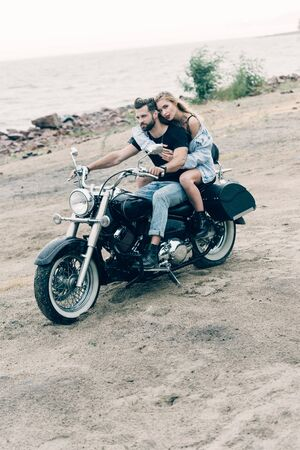 young couple of bikers riding black motorcycle at sandy beach