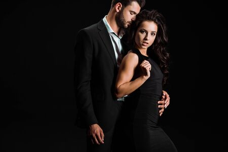 man with closed eyes hugging beautiful woman in dress looking at camera isolated on black