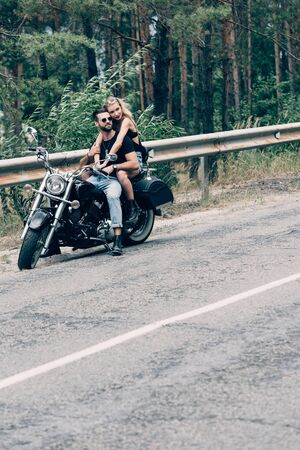 young couple of bikers hugging on black motorcycle on road near green forest