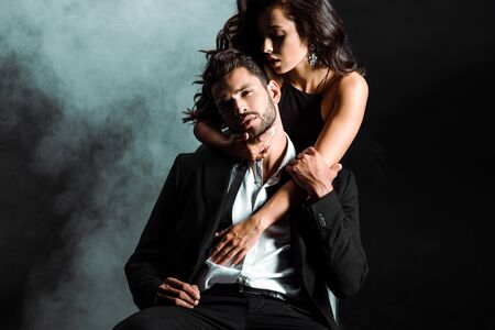 passionate young woman standing and hugging handsome bearded man on black with smoke Stockfoto
