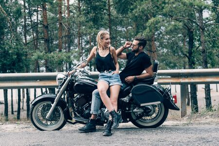 young happy couple of bikers on black motorcycle on road near green forest