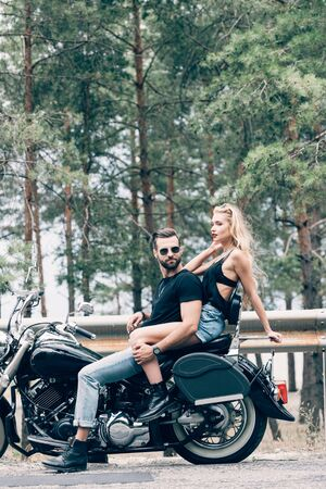 side view of sexy couple of bikers on black motorcycle on road near green forest