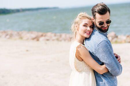 happy blonde woman hugging bearded smiling boyfriend at beach Stockfoto