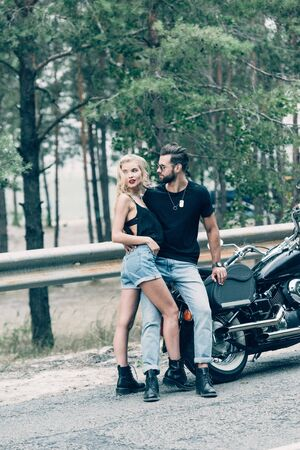 young sexy couple of motorcyclists hugging and looking away near black motorcycle on road near green forest