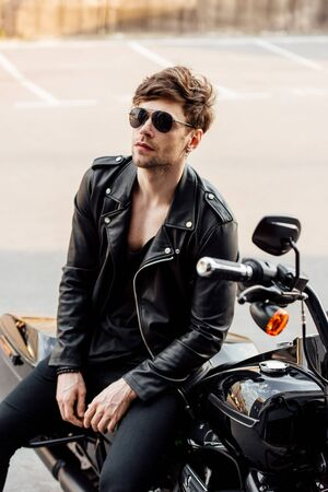 motorcyclist in leather jacket sitting on black motorcycle and looking away Reklamní fotografie