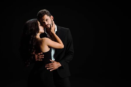 young attractive woman hugging bearded man isolated on black