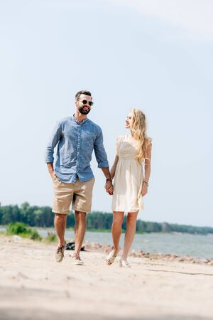 adult happy couple walking along beach and holding hands