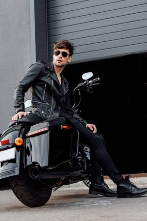full length view of motorcyclist in sunglasses and leather jacket sitting on motorcycle near opened garage Stock Photo