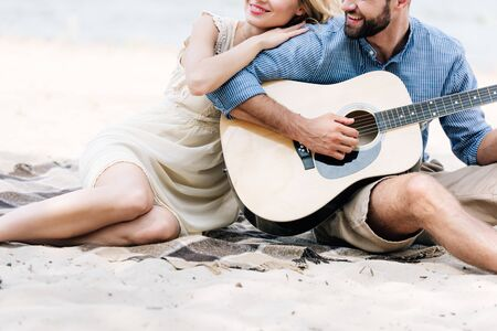 cropped view of beautiful young couple sitting on blanket with acoustic guitar at beach near sea Stockfoto
