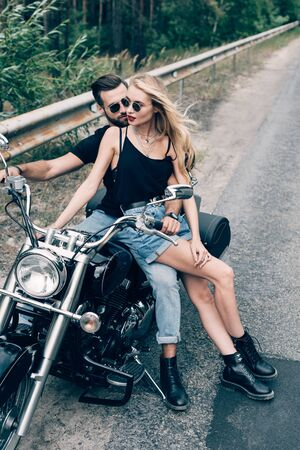 young couple of bikers sitting on black motorcycle on road near green forest