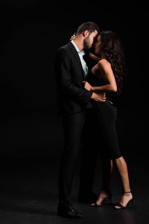 attractive girl in dress standing and kissing handsome bearded man on black