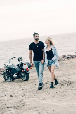 young couple of bikers in love walking and holding hands near black motorcycle at sandy beach Stockfoto