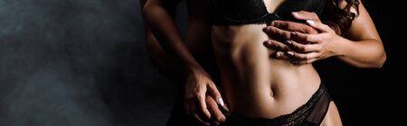 photo panoramique d'un homme étreignant une femme en sous-vêtements isolée sur fond noir avec de la fumée