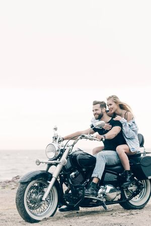happy young couple of bikers riding black motorcycle at sandy beach Stockfoto