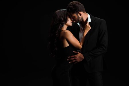 attractive girl touching suit of passionate bearded man isolated on black Stockfoto