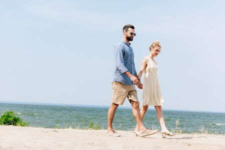 adult couple walking along sandy beach and holding hands