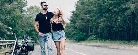 young attractive couple of bikers walking along road and embracing near black motorcycle, panoramic shot