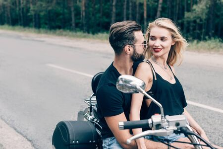 happy young couple of bikers looking at each other on black motorcycle on road