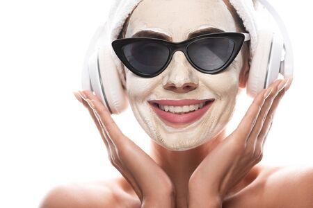 front view of nude woman in cosmetic hair band and sunglasses with facial mask listening music in headphones isolated on white