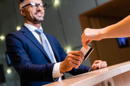 handsome businessman in suit and glasses giving credit card to woman