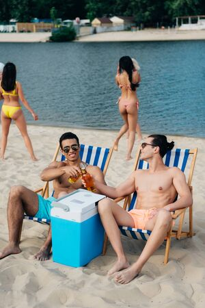 handsome multicultural friends clinking bottles of beer while sitting in chaise lounges near cooler box on beach Banco de Imagens