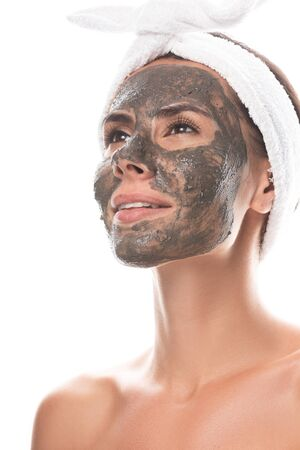 nude young woman in cosmetic hair band with clay mask on face looking away with smile isolated on white