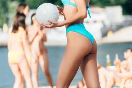 Ausgeschnittene Ansicht einer jungen Frau im Badeanzug, die Ball am Strand hält