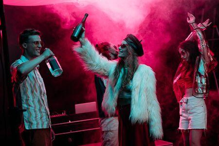 mannen en meisjes met alcohol dansen in nachtclub met roze rook Stockfoto