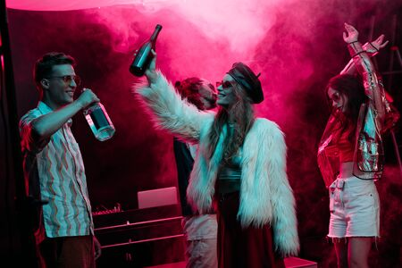 men and girls with alcohol dancing in nightclub with pink smoke Banco de Imagens
