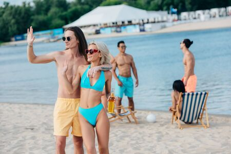 cheerful young couple waving hands while standing on beach near multicultural friends Banco de Imagens