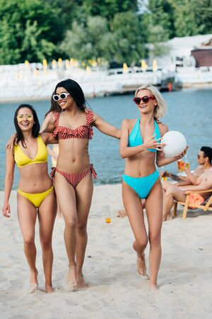 attractive young woman holding ball near beautiful, cheerful friends on beach