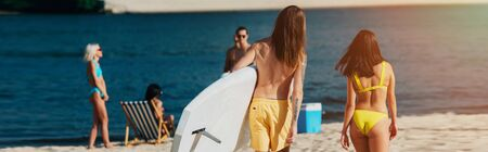 back view of young man holding surfboard near girl in swimsuit, panoramic shot Banco de Imagens