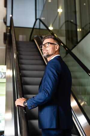 handsome and confident businessman in suit and glasses on escalator Banco de Imagens