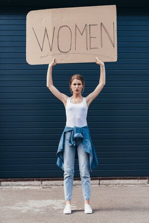 full length view of feminist holding placard with inscription women on street