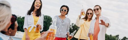panoramic shot of cheerful multicultural friends with bottles of beer having fun on beach