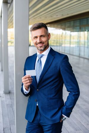 handsome businessman in formal wear with hand in pocket holding blank card