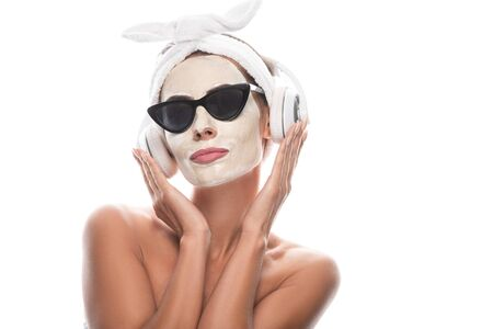 nude woman in cosmetic hair band and sunglasses with facial mask listening music in headphones isolated on white 스톡 콘텐츠