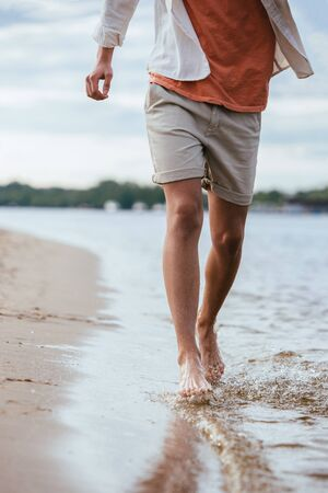 cropped view of young man in shorts running on riverside